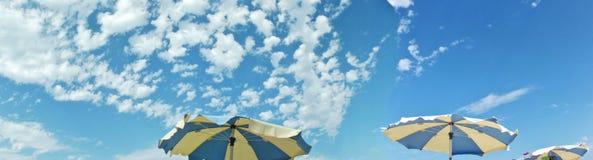 Зонтики пляжа, голубое и желтое, с голубым небом и облаками стоковые изображения rf