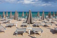 Зонтики пляжа и loungers солнца Стоковые Изображения