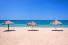Зонтики соломы на красивом тропическом пляже Стоковое Фото
