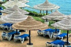 Зонтики соломы от солнца на пляже рядом с loungers солнца, Стоковое Фото