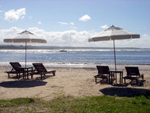 зонтики стулов пляжа Стоковые Изображения