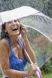 зонтик дождя мобильного телефона используя детенышей женщины Стоковая Фотография RF