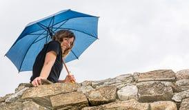 Зонтик девушки holdingan усмехаясь от стены Стоковые Изображения RF