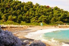 Зонтик и кровати на Milia приставают к берегу, Skopelos, Греция стоковое изображение
