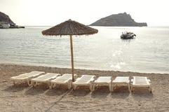 Зонтик и пустые sunbeds на песчаном пляже во время каникул Стоковое Фото