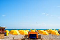 Зонтик и стул на белом песке на голубом море Стоковые Изображения RF