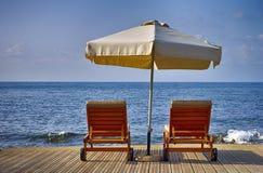Зонтик и 2 sunbeds на пляже моря Стоковое Изображение