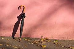 Зонтик около розовой стены Стоковая Фотография