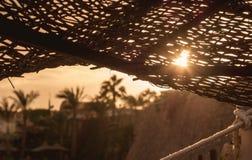 Зонтик пляжа в солнце на заходе солнца стоковое фото