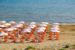 Зонтик пляжа и sunbeds на песчаном пляже в Греции Стоковые Изображения