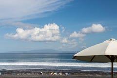 Зонтик пляжа на солнечный день, море в предпосылке Тропический пляж с отработанной формовочной смесью Красивейшее небо Остров Бал Стоковые Фото