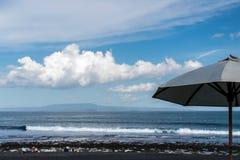 Зонтик пляжа на солнечный день, море в предпосылке Тропический пляж с отработанной формовочной смесью Красивейшее небо Остров Бал Стоковое Фото