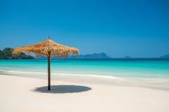 Зонтик пляжа сделанный из листьев на белом пляже перед днем моря Стоковое Изображение