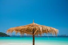 Зонтик пляжа сделанный из листьев на белом пляже перед днем моря Стоковое Изображение RF