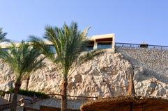 Зонтик Солнця в форме соломенной шляпы на предпосылке гостиницы на скале каменного утеса, зеленых ладоней в tropica рая Стоковое фото RF