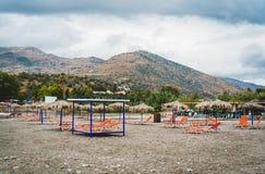 Зонтик соломы на песчаном пляже в Греции Шезлонги с зонтиками на красивом пляже в острове Крита Деревня внутри стоковое фото