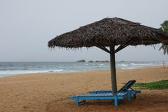 Зонтик соломы с деревянными loungers солнца на пляже Индийского океана Стоковое Изображение RF