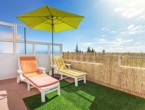 Зонтик, sunbed на террасе для загорать и ослаблять Стоковое Изображение
