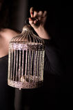 Золотая клетка в женственной руке на темной предпосылке символ свободы и кабалы в замужестве стоковое фото rf