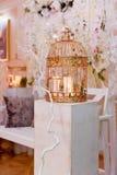 Золотая клетка с свечами на белом деревянном постаменте Зона фото свадьбы стоковые фотографии rf