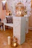 Золотая клетка с свечами на белом деревянном постаменте Зона фото свадьбы стоковая фотография