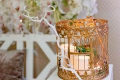 Золотая клетка с свечами на белом деревянном постаменте Зона фото свадьбы стоковая фотография rf