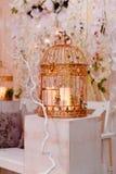 Золотая клетка с свечами на белом деревянном постаменте Зона фото свадьбы стоковые изображения