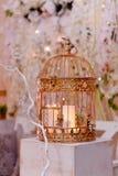 Золотая клетка с свечами на белом деревянном постаменте Зона фото свадьбы стоковое изображение