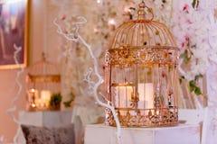 Золотая клетка с свечами на белом деревянном постаменте Зона фото свадьбы стоковое изображение rf