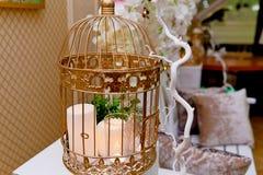 Золотая клетка с свечами на белом деревянном постаменте Зона фото свадьбы стоковые фото