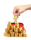 Золотая монетка в руке человека и красном портмоне изолированных на белизне Стоковые Изображения