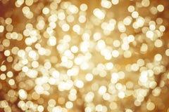 Золотая предпосылка с сверкнать естественного bokeh defocused освещает Стоковые Фотографии RF