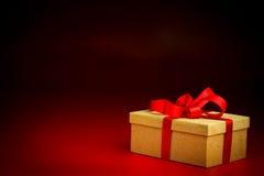 Золотая присутствующая коробка с красной лентой Стоковая Фотография RF