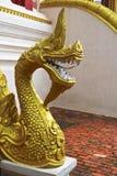 Золотая скульптура лестницы Naga в виске Lao Стоковое Изображение