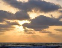 Золотая солнечность через облака распространяя над бесконечным океаном Стоковое Изображение RF