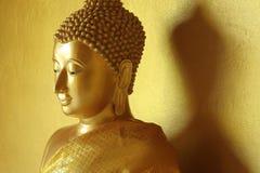 Золотая статуя Будды в золотой предпосылке Стоковое фото RF
