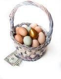 Золотистое яичко в корзине с деньгами Стоковые Фото