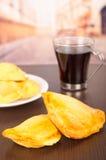 2 золотое и зажаренные тест на таблице с кофе и белым блюдом позади Стоковое Изображение