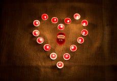 Золотое кольцо в коробке лежа в середине формы сердца свечей Стоковые Изображения RF