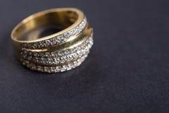 Золотое обручальное кольцо на серой предпосылке Стоковые Фото