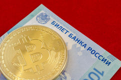 Золотое Bitcoins (цифровые виртуальные деньги) и 100 рублей Стоковое фото RF