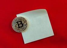 Золотое Bitcoins (цифровые виртуальные деньги) на стикере и красном backg Стоковое фото RF