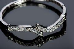 Золотой браслет с драгоценными камнями на сером цвете Стоковые Изображения RF