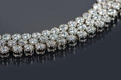 Золотой браслет с драгоценными камнями на сером цвете Стоковые Изображения