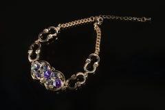 Золотой браслет с драгоценными камнями на черноте Стоковая Фотография