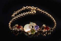 Золотой браслет с драгоценными камнями на черноте Стоковые Изображения
