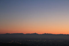 Золотой заход солнца над холмом с горизонтом гор Стоковые Фото