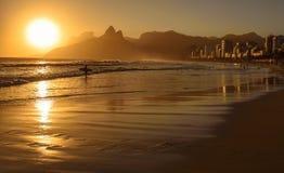 Золотой заход солнца с силуэтом горы и серфера Dois Irmaos на Ipanema приставает к берегу стоковые изображения rf