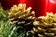 Золотой конус сосны на украшении рождества с елью и красными свечами Стоковые Изображения RF
