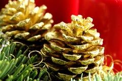 Золотой конус сосны на украшении рождества с елью и красными свечами Стоковые Изображения